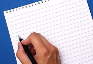 Mano con penna che scrive su blocco a righe su sfondo celeste