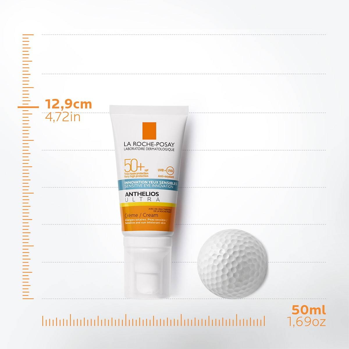 Confezione Anthelios ultra face cream SPF50+ da 50ml con pallina da golf accanto su assi cartesiani che indicano 12,9cm di altezza